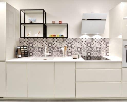Façades laquées blanc brillant, plan de travail en compact 20 mm Finitop, électroménager Bosch, hotte Elica, évier sous plan et mitigeur Blanco